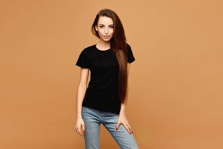 Young smiling woman with slim perfect body in a black t-shirt at the beige background, isolated. Sale advertisement mockup