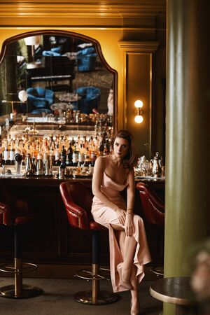 A young woman in evening dress spending time alone in a restaurant interior
