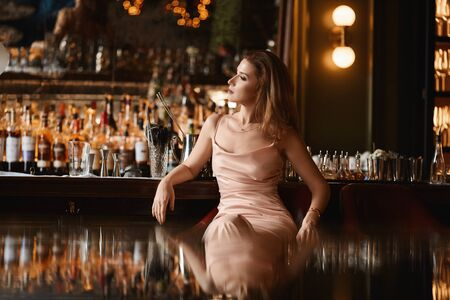 A gorgeous young woman in the evening dress sitting at the bar in the luxury interior.