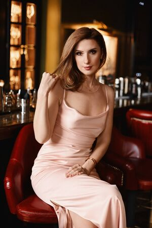 Model girl in the evening dress sitting at the bar in the luxury restaurant.