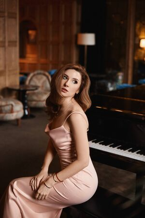 A young woman with perfect body in a long satin dress is sitting at the grand piano in the luxury interior.