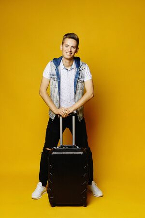 Young handsome man is holding a travel suitcase and ready to vacation, isolated over a yellow background. Standard-Bild