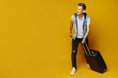 Young hipster man in casual outfit is walking with suitcases over yellow background. Travel and vacation concept.