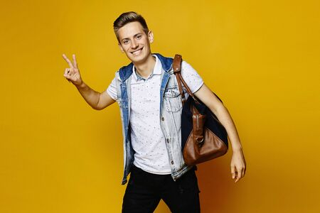 A young man in a denim outfit is holding a travel bag and showing a peace gesture, isolated over a yellow background. Young traveler.