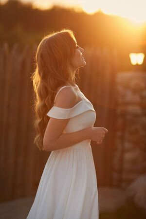 An attractive young woman in white dress is spending time outside in the park on the sunset
