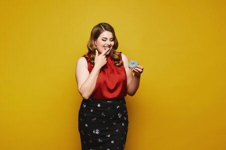 Plus-size model girl in a red satin blouse and black skirt ready to eat a tasty donut, isolated at the yellow background. Foto de archivo