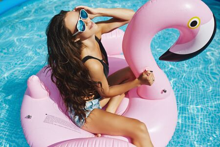 Model girl with perfect body in black bikini and sunglasses posing on an inflatable pink flamingo in the swimming pool outdoors