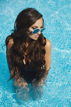A young model girl in bikini and sunglasses enjoying of a sunny summer day in the swimming pool