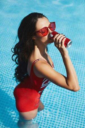 A young female model in red swimsuit and sunglasses enjoying a cold beverage in the swimming pool outdoors. 版權商用圖片