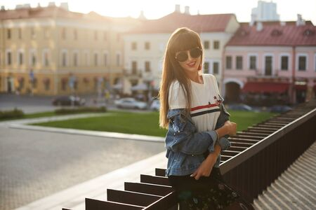 Young model girl in a denim jacket and round sunglasses is posing at the sunny street in the summer day 版權商用圖片