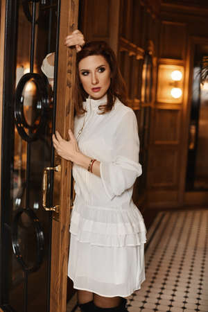 A young woman in white cocktail dress leans on the vintage door in the luxury interior.