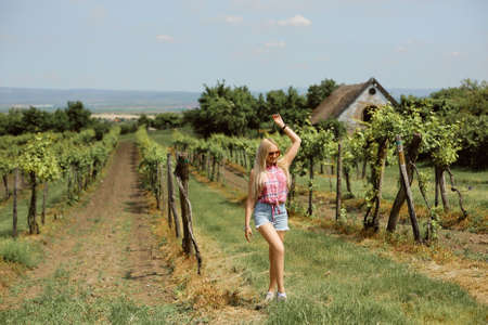A model girl in a pink shirt and denim shorts is walking through the vineyard in the countryside. Summer traveling concept Foto de archivo