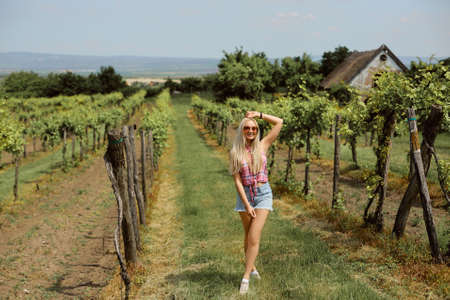 A young woman in a summer outfit posing in the countryside Foto de archivo