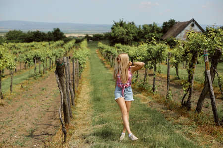 Young hipster girl is walking through the vineyard in the countryside.