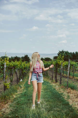 Blond model girl with slim perfect body in denim shorts and sleeveless shirt walking in the countryside. Summertime traveling
