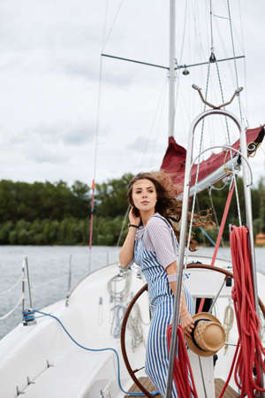 A young woman in blue striped overalls posing on the deck of a yacht on a windy summer day Foto de archivo