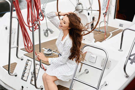A young happy woman with long beautiful hair in white dress posing on the deck of a yacht ship