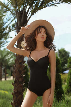 Model girl with sexy perfect body, big breasts and slim waist, in a black swimsuit and straw hat looking aside and posing outdoors at tropics Foto de archivo