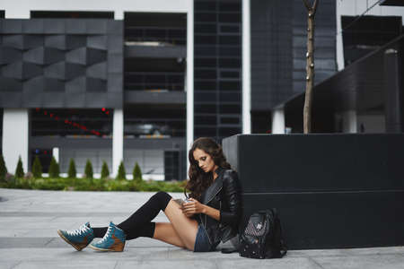 A model girl in a fashionable outfit sits outdoors and surfs the social network using her smartphone