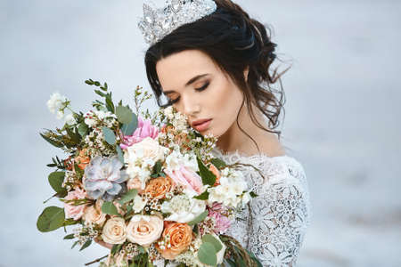 Young bride with wedding hairstyle and luxury diadem holding a big luxury bouquet of exotic flowers in her hands Foto de archivo