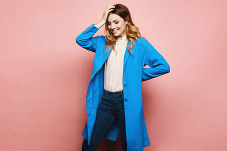 Young model girl in a blue cardigan holds her head with her hand and poses at the pink background, isolated with copy space. Sale and discount