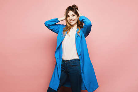A young woman in a blue coat holds her head with her hands and poses on a pink background, isolated with copy space. Advertising concept