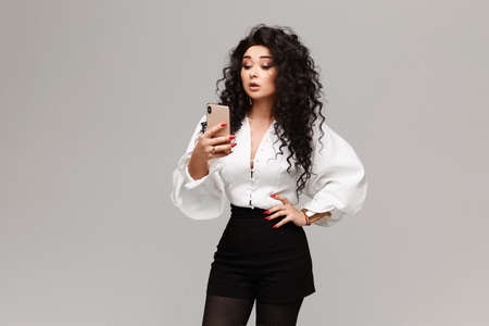 A gorgeous young woman in a fashionable outfit with a phone in her hand is surprised by something she saw on the screen in front of a white background, isolated
