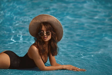 Brunette model girl with perfect sexy body in a stylish black bikini, glamorous sunglasses, and straw hat posing in the swimming pool outdoors Foto de archivo