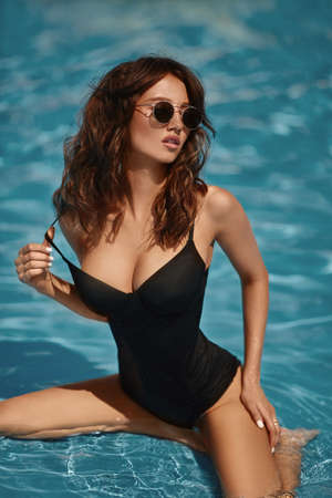 A young gorgeous woman with sexy big breasts and slim waist in a black swimsuit posing in the swimming pool outdoors on a summer day