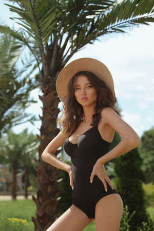 Model girl with sexy perfect body, big breasts and slim waist, in a black swimsuit and straw hat posing at the exotic resort territory