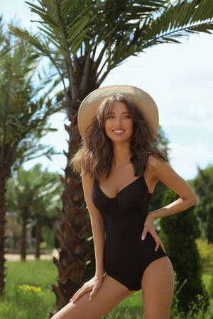 A gorgeous young woman with a perfect body in a black fashionable swimsuit and straw hat enjoying a summer day at the resort territory