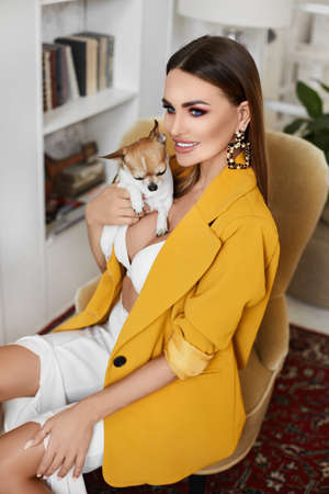 Sexy model girl with perfect body in a yellow blazer and white bra posing with cute little chihuahua dog in the interior