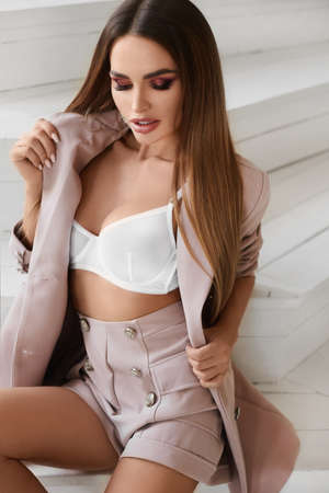 Model girl with perfect body and full lips wearing in unbuttoned jacket and white bra posing in the interior