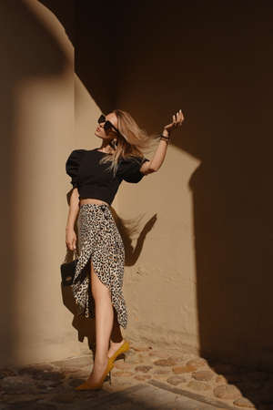 Fashion portrait of a model girl in leopard print midi skirt and black blouse posing outdoors on the summer day Foto de archivo