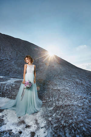 Young model girl in a luxurious wedding dress posing with a bridal bouquet with the mountains in the background