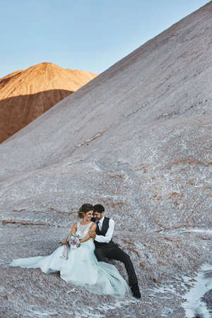 A young couple of newlyweds hugging and posing outdoors over the beautiful landscape with mountains