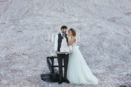 Young bride in fashionable dress and handsome groom in stylish suit posing with the luxurious wedding cake outdoors