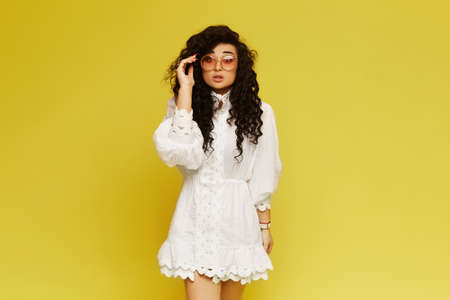A shocked brunette model girl with curly hair in a trendy dress and rounded sunglasses posing on yellow background, isolated with copy space Foto de archivo