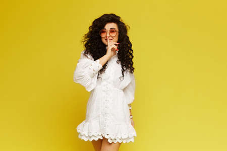 Young woman with curly hair, in a white dress and sunglasses, making gesture hush and posing on yellow background, isolated