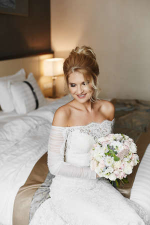 A young bride with blonde hair and wedding coiffure in lace dress sits with a bouquet of flowers on the bed at a stylish interior