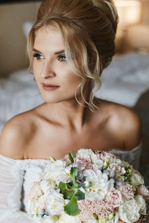Portrait of a young woman with bridal coiffure and in a wedding gown with a bridal bouquet in her hands Foto de archivo