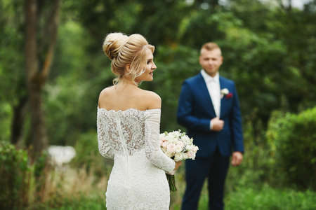 Young blonde woman with wedding coiffure in lace dress keeping a bouquet and walking to her future husband