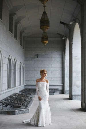 Young bride in a stylish wedding gown posing outdoors on the summer day