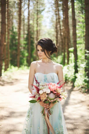 Outdoors portrait of a young bride with bridal coiffure in a wedding gown keeping the big bouquet Foto de archivo