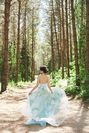 Pretty brunette woman in a long dress running away in summer forest