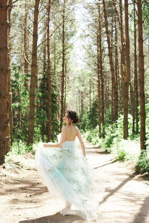 Brunette model girl in a long stylish dress looks back and runs away into the distance through the summer forest Foto de archivo