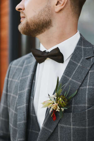 Close up cropped portrait of a handsome man, young groom in a bow tie and checkered suit with a boutonniere on the pocket
