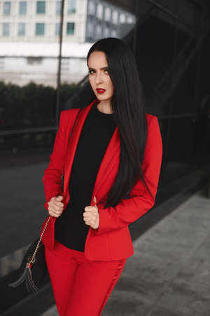 Gorgeous brunette woman with black hair in an elegant red suit looking at the camera and posing outdoors