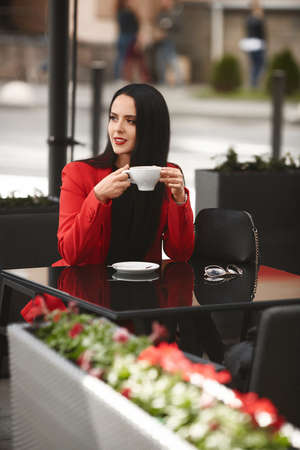 Model girl in fashionable red suit drinks coffee at the cafe table outdoors