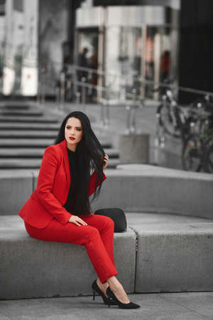 Young woman with wearing stylish red suit sits on the bench outdoors on the city street Stock fotó